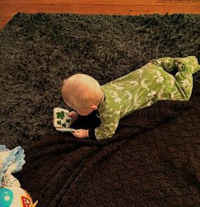 """Griffin at 5 months old, """"reading"""" his own books, turning pages one by one very intently."""