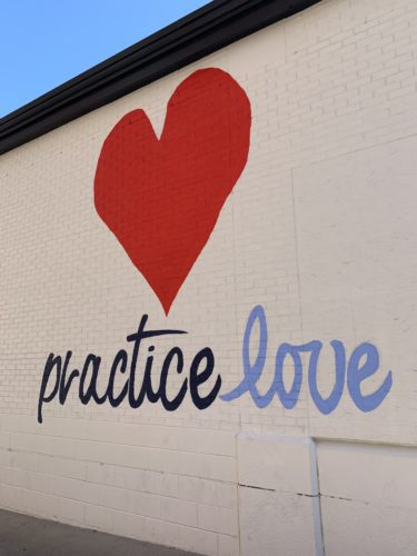 A public mural that says 'Practice Love' located in downtown Iowa City.