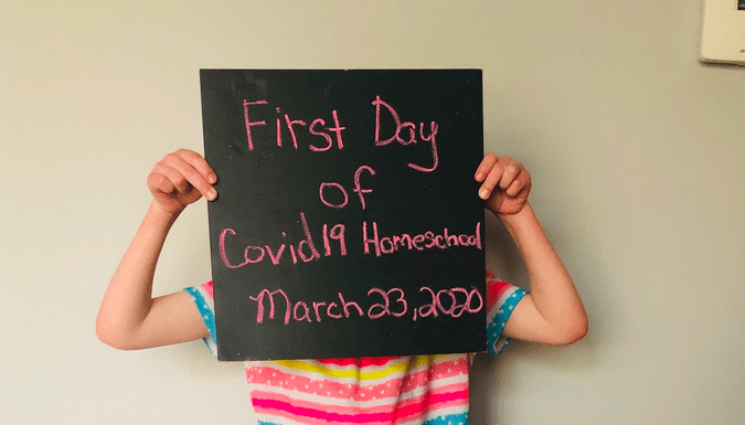 A child holds up a sign saying 'first day of covid19 homeschooling'