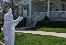 The easter bunny waves to a house and family