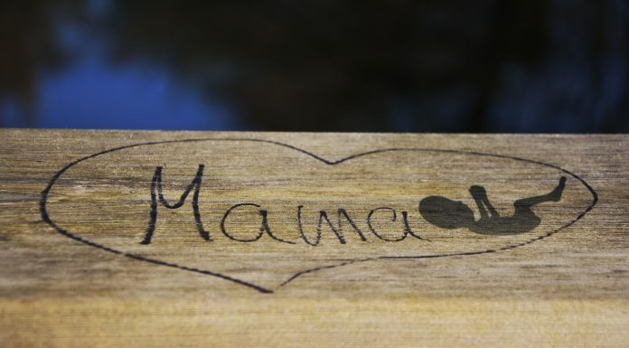 An image of a baby carved on wood.