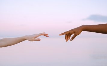 Two women reaching for hands.