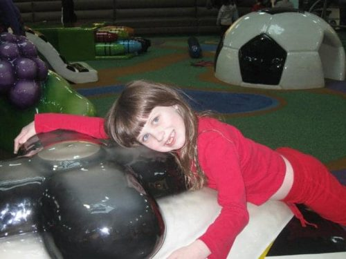 Young girl at soft play area in the mall, in front of soccer ball