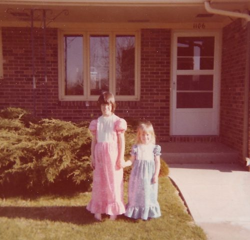 Two girls in spring dresses in front of a brick house